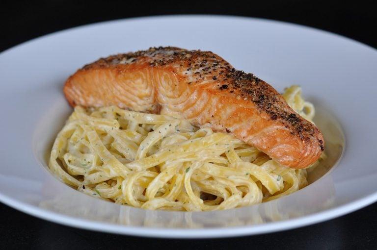 Geplanktes Lachsfilet auf Tagliatelle in Kräuter-Käse-Sauce