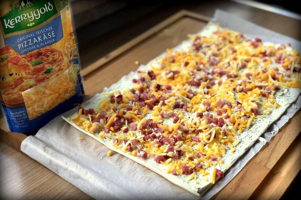 Der Blätterteig wird mit Käse bestreut blätterteigschnecken-Blaetterteigschnecken Speck Schmand Kaese 02-Blätterteigschnecken herzhaft gefüllt mit Speck & Käse