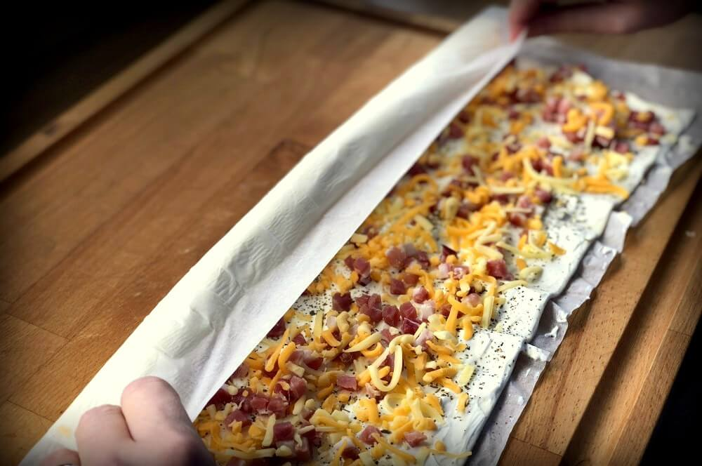 Der Blätterteig wird aufgerollt blätterteigschnecken-Blaetterteigschnecken Speck Schmand Kaese 03-Blätterteigschnecken herzhaft gefüllt mit Speck & Käse