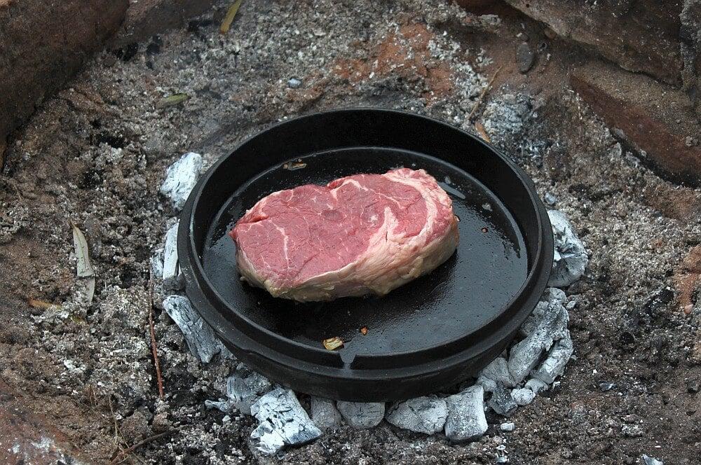 Das Steak wird im Deckel des Dutch Ovens gebraten waldpilz-chili-Waldpilz Chili Dutch Oven RibEye 04-Waldpilz-Chili & RibEye aus dem Feuer