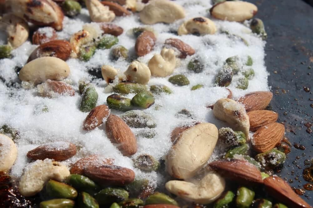 Zucker wird hinzu gegeben nusspralinen-Nusspralinen 03-Nusspralinen – Kandierte Nüsse vom Grill