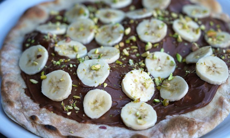 Süße Pizza mit Schokolade, Bananen und Pistazien