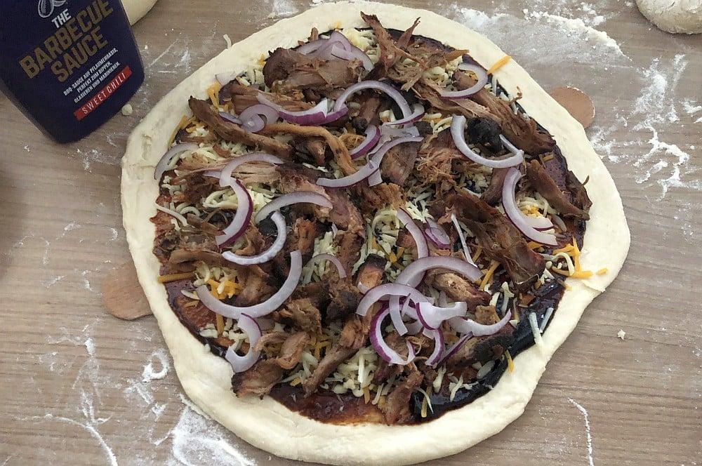 Die Pulled Pork Pizza ist fertig belegt pulled pork pizza-Pulled Pork Pizza 02-Pulled Pork Pizza vom Grill mit roten Zwiebeln