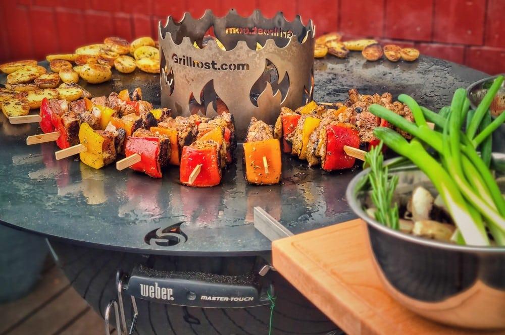 Spieße und Kartoffeln auf der Feuerplatte für Kugelgrills feuerplatte für kugelgrills-Feuerplatte Kugelgrill 80cm Grillrost 08-Feuerplatte für Kugelgrills von Grillrost.com im Test