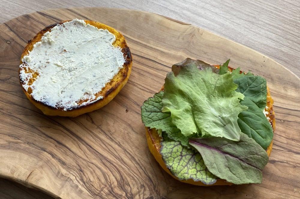 Die Buns werden mit Kräuterfrischkäse bestreichen und mit Salat belegt wildburger-Wildburger Kuerbis Bun 02-Wildburger im Kürbis-Bun